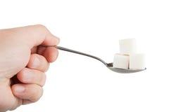 Entregue guardar uma colher em que o açúcar cuba Fotografia de Stock Royalty Free