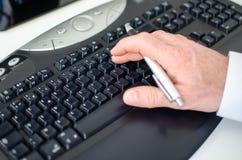 Entregue guardar uma pena e a datilografia em um teclado Foto de Stock