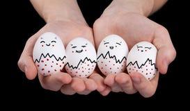 Entregue guardarar ovos bonitos com smiley engraçados da face fotografia de stock royalty free