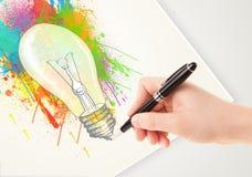 Entregue a ideia colorida de tiragem a ampola com uma pena Fotos de Stock