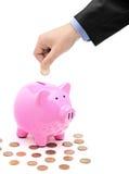 Entregue a introdução de uma moeda em um banco piggy cor-de-rosa Imagem de Stock