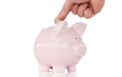 Entregue a introdução de uma moeda em um banco piggy cor-de-rosa Fotografia de Stock