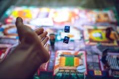 Entregue a lances os dados no fundo dos jogos de mesa Fotos de Stock Royalty Free