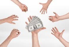 Entregue manter diversas notas de dólar e outras mãos que tentam alcançar para elas fotos de stock
