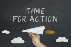 Entregue manter o avião de papel e o texto escritos no quadro-negro: Hora para a ação fotos de stock