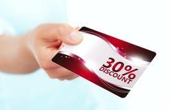 Entregue manter o cartão vermelho do disconto isolado sobre o branco Foto de Stock