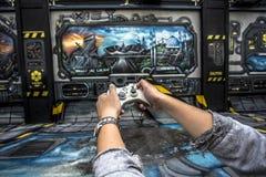 Entregue manter o controlador do jogo redigido no fundo do jogo no cinza, no azul e na laranja fotografia de stock