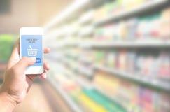 Entregue manter o telefone esperto com compras na mercearia em linha na tela imagens de stock royalty free