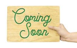 Entregue manter a placa de madeira com vinda logo palavra isolada no branco imagens de stock royalty free