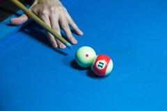 Entregue manter a sugestão da vara do bilhar em uma mesa de bilhar pronta à bola do tiro Fotos de Stock Royalty Free