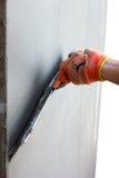 Entregue a massas de vidraceiro uma parede pela faca de massa de vidraceiro para a fachada Foto de Stock Royalty Free