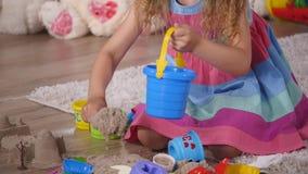 Entregue a menina loura pequena bonito que joga a areia em um estúdio Fim acima filme