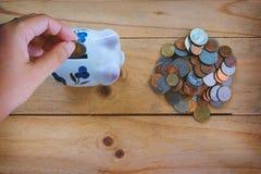 Entregue a moeda da economia ao mealheiro e uma pilha de moedas do baht tailandês na tabela de madeira Fotos de Stock