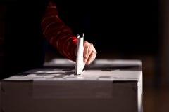 Entregue a moldação de um voto na urna de voto Foto de Stock Royalty Free