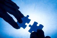 Entregue mover duas partes coloridas azul do enigma - contato azul Fotos de Stock