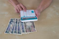 Entregue a mulher com as cédulas japonesas dos ienes da moeda e calc da utilização Foto de Stock Royalty Free