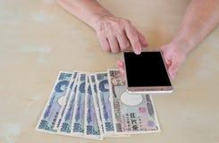Entregue a mulher com as cédulas japonesas dos ienes da moeda e a utilização esperta Fotografia de Stock Royalty Free
