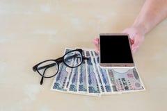 Entregue a mulher com as cédulas, vidros e u japoneses dos ienes da moeda Foto de Stock Royalty Free
