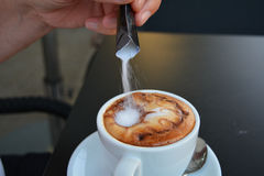 Entregue o açúcar de derramamento no cappuccino quente Foto de Stock Royalty Free