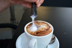 Entregue o açúcar de derramamento no cappuccino quente Imagem de Stock