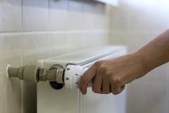 Entregue o ajuste do termostato do botão da válvula do radiador do aquecimento foto de stock royalty free
