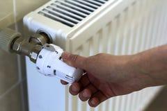 Entregue o ajuste do termostato do botão da válvula do radiador do aquecimento imagem de stock