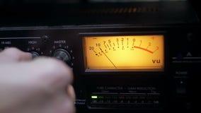Entregue o ajuste dos botões em um compressor audio de funcionamento em um estúdio de gravação sonora video estoque