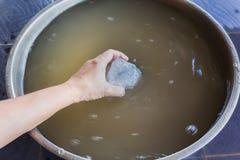 Entregue o alume do mergulho na água enlameada à água enlameada precipitado clara, a Fotografia de Stock