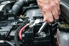Entregue o aperto de uma braçadeira de um motor de automóveis com uma chave Imagem de Stock