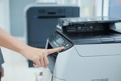 Entregue o botão da imprensa no painel da máquina da cópia do varredor ou do laser de impressora no escritório fotografia de stock royalty free