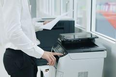 Entregue o botão da imprensa no painel da máquina da cópia do varredor ou do laser de impressora no escritório foto de stock