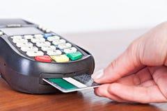 Entregue o cartão de crédito do impulso em uma máquina de cartão do crédito Foto de Stock Royalty Free