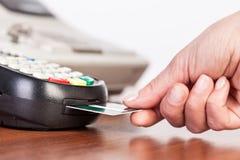 Entregue o cartão de crédito do impulso em uma máquina de cartão do crédito Fotos de Stock Royalty Free