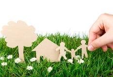 Entregue o corte do papel da preensão da família sobre a grama verde. fotos de stock