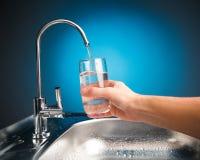 Entregue o derramamento de um vidro da água da torneira de filtro Imagem de Stock Royalty Free