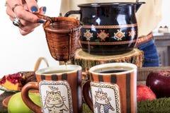 Entregue o derramamento do copo de chá para o chá através de um filtro em dois c Fotografia de Stock