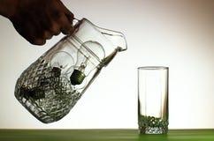 Entregue o derramamento do jarro de ampolas no vidro fotos de stock