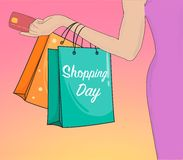 Entregue o dia de compra tirado com a mão da mulher que guarda o cartão e os sacos de banco Foto de Stock Royalty Free
