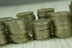 Entregue o empilhamento de moedas de ouro com os rebentos que crescem nas moedas, alinhadas com construções, dinheiro do negócio  imagem de stock royalty free