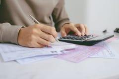 Entregue o homem que faz finanças e calcule-o na mesa sobre o custo em casa imagem de stock