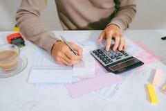 Entregue o homem que faz finanças e calcule-o na mesa sobre o custo em casa foto de stock royalty free