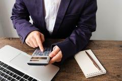 Entregue o homem que faz finanças e calcule-o na mesa sobre o custo em casa imagens de stock royalty free