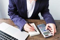 Entregue o homem que faz finanças e calcule-o na mesa sobre o custo em casa imagens de stock