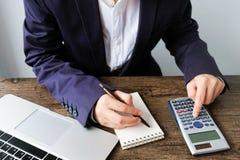 Entregue o homem que faz finanças e calcule-o na mesa sobre o custo em casa fotos de stock royalty free