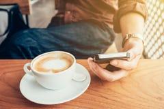 Entregue o homem que usa o telefone na cafetaria com filtro do vintage Fotografia de Stock Royalty Free