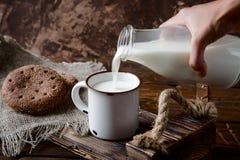 Entregue o leite de derramamento da garrafa em um copo Imagem de Stock