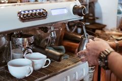 Entregue o leite do vapor do barista na caneca do metal no fabricante de café fotografia de stock