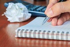 Entregue o livro de notas da escrita na tabela de madeira, foco seletivo Fotos de Stock Royalty Free