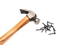Entregue o martelo com a pilha dos pregos sobre o branco Fotografia de Stock