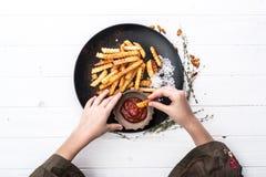Entregue o mergulho de uma microplaqueta de batata na opinião superior de ketchup de tomate Imagem de Stock Royalty Free